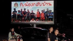 Motorists pass by a billboard displaying a photograph of the Thai children's football team