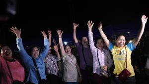 Volunteers celebrate at a makeshift press centre in Mae Sai district of Chiang Rai province on July 10, 2018, after the twelve boys and their football coach were rescued.(AFP/Ye Aung THU)