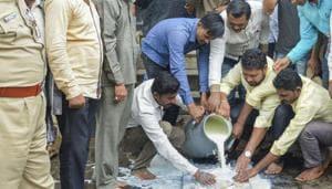 Swabhimani Shetkari Sanghatana activists pour milk in front of a temple in Karad, Maharashtra, on Monday.(PTI Photo)