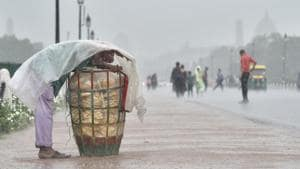 A vendor covers himself with a plastic sheet during heavy rain at Rajpath, in New Delhi, on Monday, July 16, 2018.(Ajay Aggarwal/HT PHOTO)