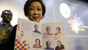 Ramon Magsaysay Award Foundation president Carmencita Abella poses with pictures of this year's awardees, regarded as an Asian version of the Nobel Peace Prize, in Manila, Philippines, Thursday.(AP)