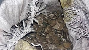 The pot, containing 329 coins weighing nearly four kilos, was found when the ground was being dug to construct the main gate of the Bhairav Temple in the village located in Khirsu block.(HT PHOTO)