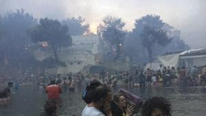 Mati : In this Monday, July 23, 2018 image from video provided by Elia Kallia, people escaping wildfires wade into the waters of the