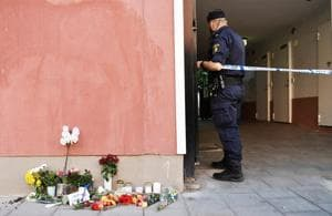 A police officer stands at a cordon, next to flowers and condolences outside the place where a 20 year old man with Down Syndrome, who was carrying a toy gun, was shot and killed by the police in Stockholm, Sweden.(REUTERS)