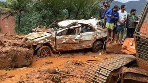 People inspect a damaged car following a landslide, triggered by heavy rains, in Idukki.(PTI Photo)