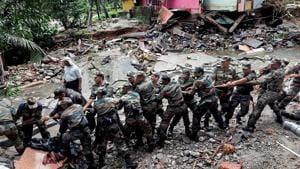 Soldiers clear debris off a road in a flood affected area at Wayanad.(PTI)