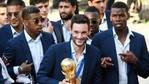 France's goalkeeper Hugo Lloris holds the World Cup trophy next to France's midfielder Paul Pogba (right) as they arrive for a reception at the Elysee Presidential Palace on July 16.(AFP)