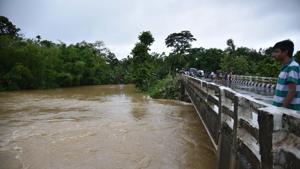 People stand on a bridge at a flooded village of Bokakhat in Golaghat district of Assam.(HT File Photo/Representative image)