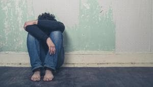 A sad and depressed young man is sitting on the floor in an empty room.(Getty Images/iStockphoto)
