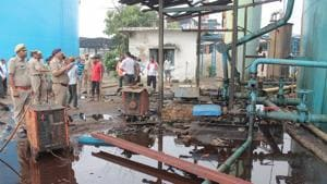 People stand near the site of explosion at a petro-chemical factory where a methane gas boiler tank exploded killing six workers, in Bijnor on September 12.(HT Photo)