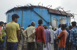 People stand near the site of explosion at a petro-chemical factory, where a methane gas boiler tank blasted killing six workers, in Bijnor on September 12.(PTI Photo)