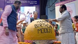 HRD minister Prakash Javadekar and minority affairs minister Mukhtar Abbas Naqvi at the unveiling of a 568 kg laddoo on PM Modi's 68th birthday.(Sonu Mehta/HT Photo)