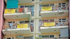 Residents of have hung huge yellow banners from their balconies, each listing the issues faced by them.(Sakib Ali/HT photo)