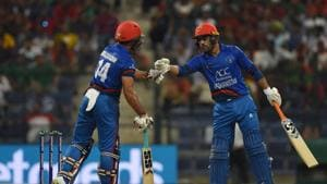 Afghan batsman Gulbadin Naib (L) and teammate Rashid Khan greet each other during the one day international (ODI) Asia Cup cricket match between Bangladesh and Afghanistan at the Sheikh Zayed Stadium in Abu Dhabi.(AFP)