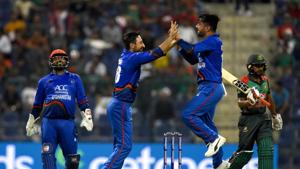 Afghan cricketer Rashid Khan (2R) celebrates with teammate Rahmat Shah (2L) and wicketkeeper Mohammad Shahzad (L) after he dismissed Bangladesh batsman Mehidy Hasan Miraz.(AFP)