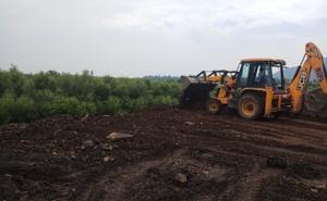 A JCB levels debris dumped near mangroves at Navin Sheva.(Bachchan Kumar/HT)