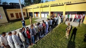 Jammu: Security persoonel stands guard as people wait in queues to cast their votes for muncipal elections in Ranbir Singh Pura near Jammu, Monday, Oct 8, 2018. (PTI Photo) (PTI10_8_2018_000026B)(PTI)