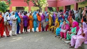 People wait in a queue to cast their votes at a polling station during municipal elections in Jammu, on Monday.(PTI)