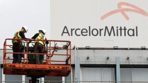 Workers stand near the logo of ArcelorMittal, the world's largest producer of steel, at the steel plant in Ghent, Belgium.(Reuters File Photo)