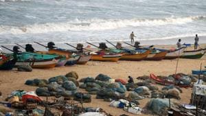 Fishermen stand along a beach beside fishing boats on the coast of the Bay of Bengal, in Chennai on November 12.(AFP Photo)