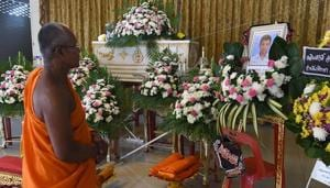 A monk looks at a portrait of thirteen-year-old Muay Thai boxer Anucha Tasako during is funeral at a Buddhist temple in Samut Prakan province on November 14, 2018(AFP/Getty Images)