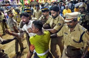 Police personnel detain the devotees who were staging 'Namajapa' protest against the police restrictions at Sannidhanam, in Sabarimala.(PTI Photo)