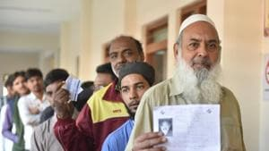 Voters show their identity card as they stand in a queue at a polling station, in Jahangirabad, Bhopal, India, on Wednesday.(HT Photo)