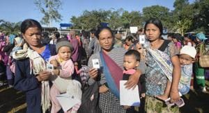 Bru tribal women show their identity card as they wait to cast their vote at a polling station for the state elections, at Kanhmun, Mizoram on November 28.(PTI Photo)