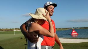 Jon Rahm Spain walks off the 18th green with fiancee Kelley Cahill after winning the Hero World Challenge in Bahamas.(AFP)