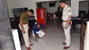 Police officials inspect the spot at Hotel Kolhapuri, where the businessman was shot at. The hotel is located on the service road of the Pune-Mumbai highway in Tathawade.(HT PHOTO)