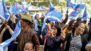 Mizoram assembly elections 2018: Mizo National Front (MNF) workers hold up party flag as they celebrate the party's victory in the Assembly elections, in Aizawl.(PTI)
