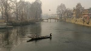 A boatman makes his way through partially frozen water of Dal Lake on a cold morning in Srinagar, Jammu and Kashmir. (Photo by Waseem Andrabi/ Hindustan Times)(HT Photo)
