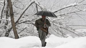 A man walks through a snow-covered road during fresh snowfall at Tangmarg road about 38 kilometers from Srinagar, Jammu and Kashmir, on Wednesday, January 2, 2019.(Waseem Andrabi / HT Phot o)