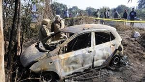 Police inspect a burned car near Sambalki village, Sector 82 in Mohali on Friday.(Anil Dayal/HT PHOTO)