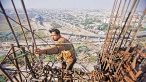 A labourer works at the construction of a residential complex at Noida.(REUTERS)