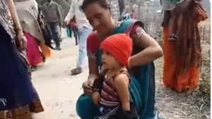 The video of a mother removing a black jacket of her crying three-year-old child on the instructions of security personnel before entering Chief Minister Sarbananda Sonowal's function in Biswanath district on Tuesday morning has drawn sharp criticism from the public(Voice of Assam/Twitter)