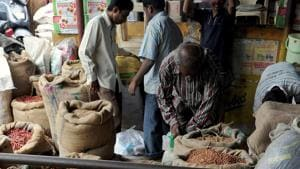 Workers and customers look through the goods at a wholesale food grain and commodities shop in the Agricultural Product Marketing Committee (APMC) Yard in Bangalore.(AFP file photo)