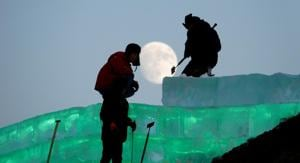 The moon shines as workers prepare an ice sculpture ahead of the Harbin International Ice and Snow Sculpture Festival in China.(REUTERS/Representative image)