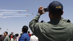 An Indian Air Force (IAF) officer films Sarang, a helicopter display team of IAF's Dhruv choppers, perform aerobatic maneuvers on the third day of Aero India 2019 at Yelahanka air base in Bangalore, India, Friday, Feb. 22, 2019. Aero India is a biennial event with flying demonstrations by stunt teams and militaries and commercial pavilions where aviation companies display their products and technology.(AP)