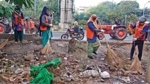 MCG contractual workers cleaning garbage near Huda City Centre fire station on Sunday.(Yogendra Kumar/HT PHOTO)