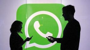 People are seen as silhouettes as they check mobile devices whilst standing against an illuminated wall bearing WhatsApp Inc's logo in this arranged photograph in London, UK.(Bloomberg)