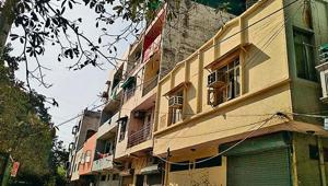 The woman threw her son first from the terrace on the road and then her daughter on the roof of the adjacent yellow building on Monday.(HT Photo)