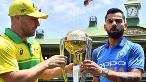 Virat Kohli (R) and his Australian counterpart Aaron Finch pose with the ICC Cricket World Cup trophy.(AFP)