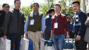 Polling officials head for polling stations with carrying the Electronic Voting Machines (EVM) from the distribution centre in Gangtok on Wednesday.(ANI)
