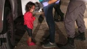 A two-year-old Honduran asylum seeker cries as her mother is searched and detained near the U.S.-Mexico border.(AFP)