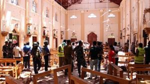 TOPSHOT - Sri Lankan security personnel walk through debris following an explosion in St Sebastian's Church in Negombo, north of the capital Colombo, on April 21, 2019.(AFP)