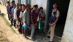 A CRPF officer stands guard at the polling station as the voters in a queue to cast vote during the general election at village Hajaripara in Agartala on Tuesday.(ANI file photo)