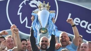 Manchester City's Spanish manager Pep Guardiola holds up the Premier League trophy as he's surrounded by his staff after their 4-1 victory in the English Premier League football match between Brighton and Hove Albion and Manchester City(AFP)