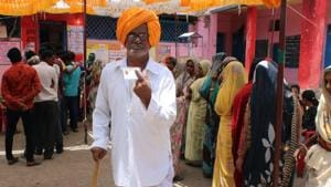 Madhya Pradesh, May 19 (ANI): Voter shows his ink-marked finger and voter ID card at a polling station after casting their vote at Rajod village in Dhar district in Madhya Pradesh on Sunday.(ANI)