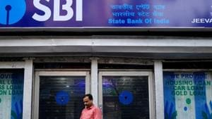 A man checks his mobile phones in front of State Bank of India (SBI) branch(REUTERS)